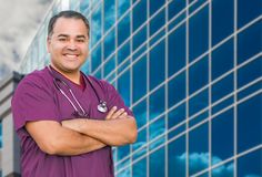 Hispanic Male Nurse In Front Of Hospital Building. Hispanic Male Nurse In Front Of a Hospital Building royalty free stock photos