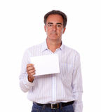 Hispanic male standing and holding a card. Portrait of a hispanic male standing and holding a blank white card while looking at you on isolated background Royalty Free Stock Photo