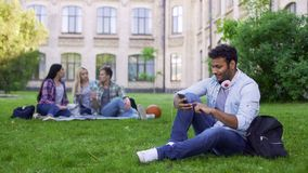 Hispanic male student sitting on grass and using cellphone, app for acquaintance. Stock photo stock image