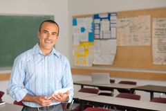 Hispanic Male Teacher. This image shows a Hispanic Male Teacher in his classroom Stock Photo