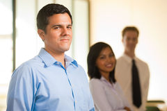Hispanic Male Team Leader Row. A singled out handsome hispanic male heads a line of cheerful colleagues Royalty Free Stock Photos