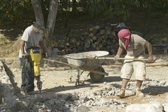 Hispanic males breaking concrete. With yellow jackhammer and shovel rocks Royalty Free Stock Image