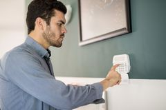 Hispanic man arming his alarm system. Profile view of a young Hispanic man using a keypad to arm his home alarm system before leaving Stock Photography