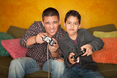 Hispanic Man and Boy Playing Video game Royalty Free Stock Images