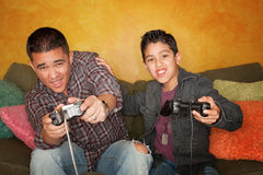 Hispanic Man and Boy Playing Video game Royalty Free Stock Image