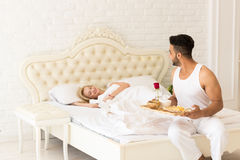 Hispanic Man Bring Breakfast To Sleeping Woman In Morning Tray With Red Rose Flower, Young Couple Stock Photo