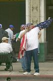 Hispanic man on cellphone with American flag Stock Photography