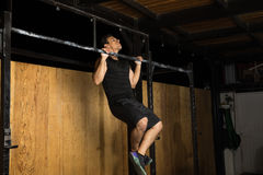 Hispanic man doing chin-ups at the gym. Handsome young Hispanic man doing some chin-ups as part of his workout at a cross-training gym Stock Image