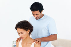 Hispanic man doing a massage to his beautiful wife. On their bed Stock Photography