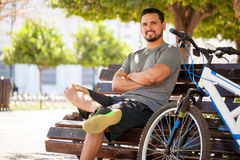 Hispanic man exercising on his bicycle. Handsome young Hispanic man ready to exercise on his bicycle around the city and smiling Royalty Free Stock Photo