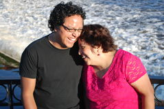 Hispanic man and his mother laughing by a river stock photo