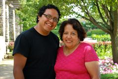 Hispanic man and his mother smiling outdoors. A Hispanic man and his mother relaxing at a beautiful park Royalty Free Stock Photo