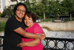 Hispanic man and his mother smiling outdoors. A Hispanic man and his mother relaxing at a beautiful park.  The son is hugging his mother Stock Photography