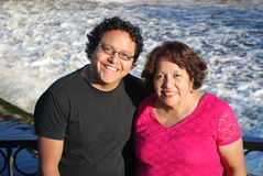Hispanic man and his mother smiling by a river. A Hispanic man and his mother relaxing at a beautiful park in front of a river Royalty Free Stock Photos
