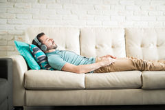 Listening to meditation music. Hispanic man on his 30s lying down on the sofa wearing casual clothes and listening to meditation music royalty free stock photo