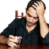 Hispanic man holding an alcoholic drink and suffering a headache Stock Photos