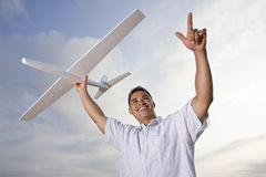 Hispanic man holding model airplane over head Stock Image