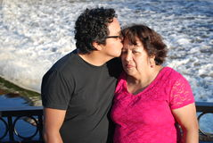 Hispanic man kisses his mother by a river. A Hispanic man kisses his mother as they relaxing at a beautiful park in front of a river Stock Photos