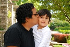 Hispanic man kissing his adorable son outdoors Royalty Free Stock Photos