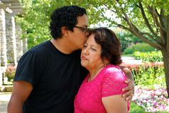 Hispanic man kissing his mother outdoors Royalty Free Stock Photo