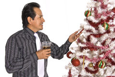 Hispanic man looking at a decorated Christmas Tree Stock Images