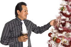 Hispanic man looking at a decorated Christmas Tree Royalty Free Stock Photo