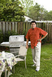 Hispanic man next to backyard grill Stock Photography