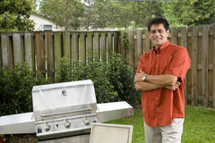 Hispanic man next to backyard grill Royalty Free Stock Photo