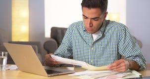 Hispanic man paying bills at home Stock Image