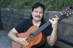 Hispanic man playing acoustic guitar outdoors Stock Image