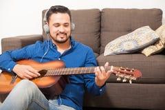 Hispanic man playing the guitar with headphones Royalty Free Stock Image