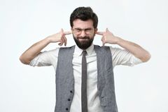 Hispanic man plugs ears with fingers, keeps eyes closed, ignores loud noise or music. Stressful bearded hispanic man plugs ears with fingers, keeps eyes closed stock image