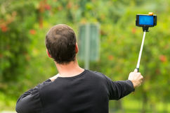 Hispanic man posing with selfie stick in park Stock Images