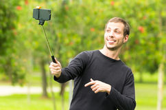 Hispanic man posing with selfie stick in park Royalty Free Stock Photography