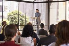 Hispanic man presenting business seminar leaning on lectern Royalty Free Stock Photos