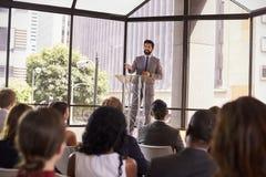 Hispanic man presenting business seminar to audience stock photo
