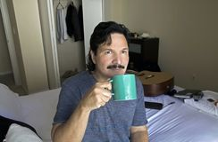 Man sitting on bed sipping from cup. Hispanic man sits on his bed in his bedroom while sipping from a cup Stock Photography