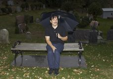 Hispanic man sitting with umbrella in cemetery Royalty Free Stock Photo