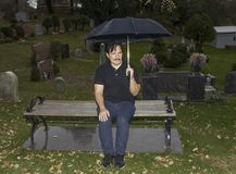 Hispanic man sitting with umbrella in cemetery Stock Photo