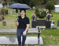 Hispanic man sitting with umbrella in cemetery Stock Photography