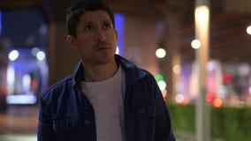 Hispanic man thinking while exploring the city streets at night