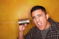 Hispanic man with tin can telephone. Attractive Hispanic man with tin can telephone Royalty Free Stock Photos