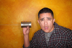 Hispanic man with tin can telephone. Attractive Hispanic man with tin can telephone Royalty Free Stock Images