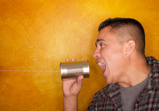 Hispanic man with tin can telephone. Attractive Hispanic man with tin can telephone Stock Photo