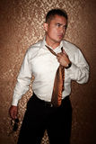 Hispanic man tugging on his tie. Handsome Hispanic man tugging on his tie Royalty Free Stock Photography