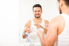 Hispanic man using gel to style his hair. Portrait of a happy young Hispanic man styling his hair with some gel in front of a mirror in the bathroom Stock Photography
