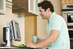 Hispanic man using home computer Royalty Free Stock Photos