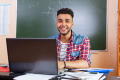 Hispanic Man Using Laptop Computer, Student In University Classroom At Desk Over Chalk Board Stock Images