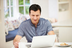 Hispanic Man Using Laptop In Kitchen At Home Stock Image