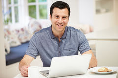 Hispanic Man Using Laptop In Kitchen At Home. Smiling To Camera Royalty Free Stock Photography